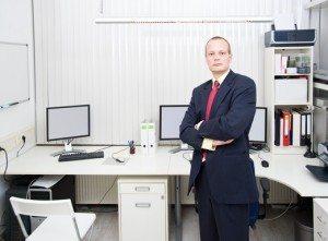 Confiant homme d'affaires à la recherche , posant devant un bureau bien équipé , représentant un propriétaire de petite entreprise