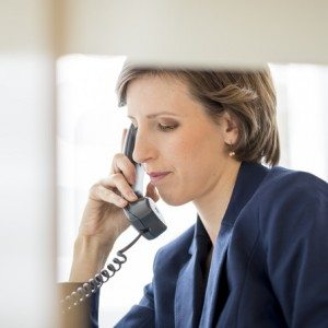 View through an internal office partition of a successful young businesswoman sitting at her desk making a phone call on a landline telephone, profile view.
